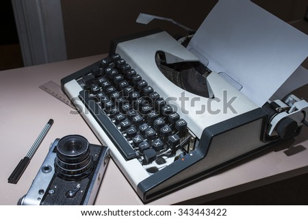 an old typewriter with the camera on the table