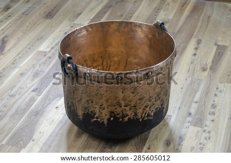 An old used copper kettle over elm wood. - stock photo