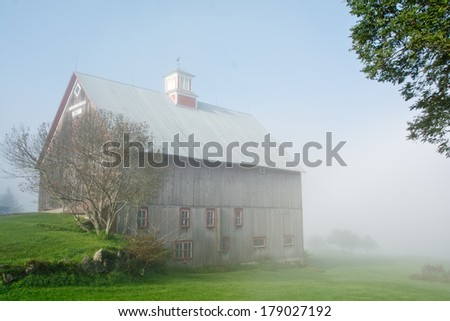 An old Vermont barn appears out of a thick morning mist. - stock photo