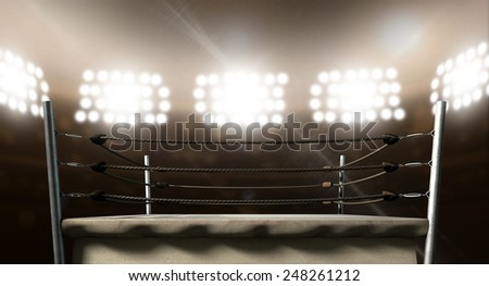 An old vintage boxing ring surrounded by ropes spotlit by floodlights in an arena setting at night - stock photo