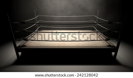An old vintage boxing ring surrounded by ropes spotlit in the middle on an isolated dark background - stock photo