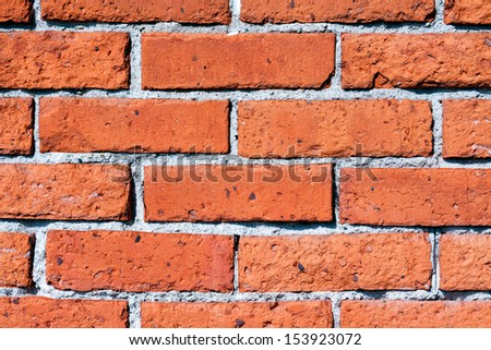 An old wall is constructed of orange red clay bricks showing a rustic and worn texture. - stock photo