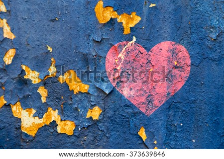 An old wall with paint peeling off and red hearts - stock photo