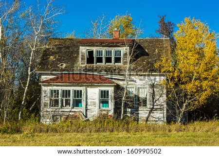 An old weather and rustic abandoned farm house. - stock photo
