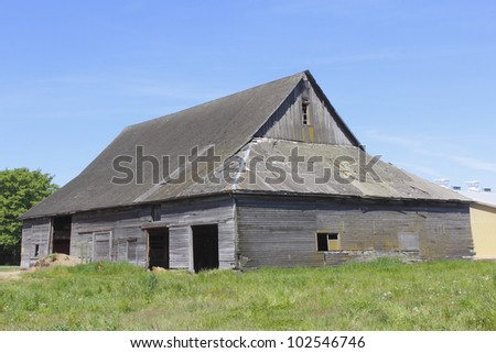An old, weathered barn stands hunched and leaning in the mid-day sun/An Old Weathered Barn/A weather-beaten barn - stock photo