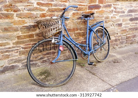An old weathered blue bicycle with basket parked against a wall  - stock photo