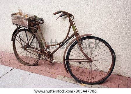 An old weathered rusty bicycle with basket parked against a wall