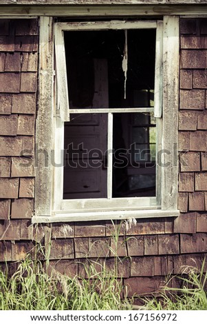 An old weathered window on an abandoned house
