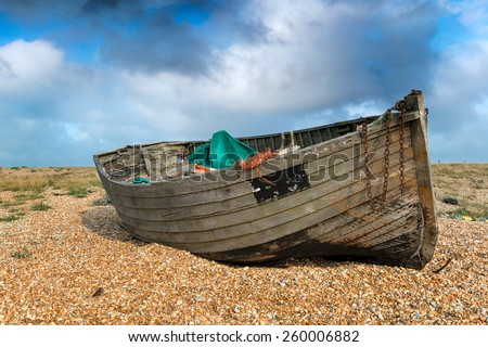 An old weathered wooden fishing boat under a blue sky on a shingle beach - stock photo