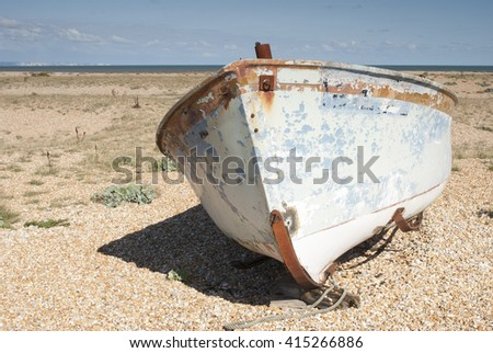 An old white abandoned fishing boat stranded on a beech. - stock photo