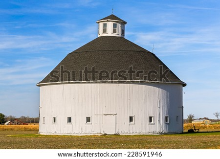 An old white round barn stands on a farm in America's Midwest. - stock photo