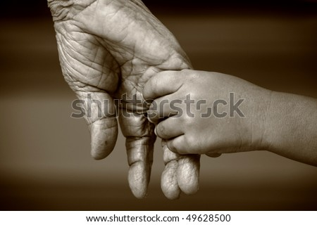 An old woman and a kid holding hands together - stock photo