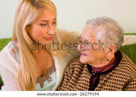 An old woman and a younger one sitting close to each other, talking - part of a series. - stock photo