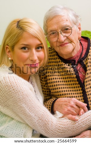 An old woman and her grandchild sitting close to each-other (focus on the young woman) - part of a series. - stock photo