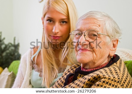 An old woman looking at the camera, a younger one in the background - part of a series. - stock photo