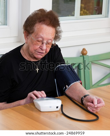 An old woman measured her blood pressure - stock photo