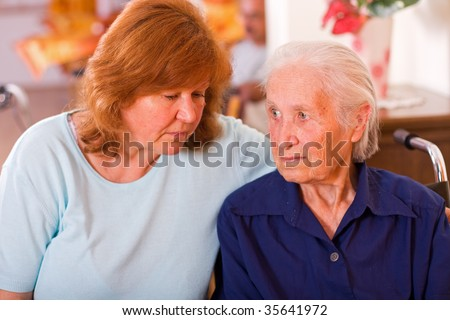 An old woman next to a mature one, a mother and a daughter, the elderly woman is sitting on a wheelchair having a worried facial expression. - stock photo