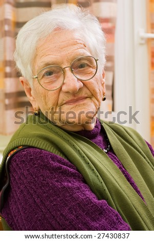 An old woman's portrait at her home. - stock photo