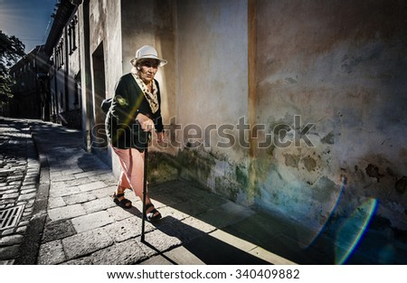 An old woman walking down the street the morning of Lviv, Ukraine, 06/21/2014 - stock photo