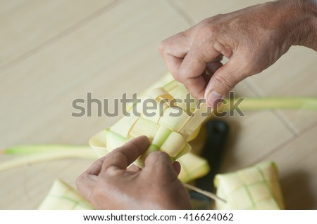 An old women preparing a South East Asian rice cakes bundle or dumpling rice or ketupat, often prepared for festivities and celebratory occasions. top view