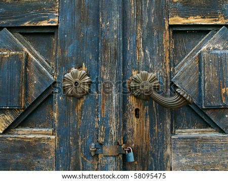 an old wood door with metal handle and new blue lock - stock photo