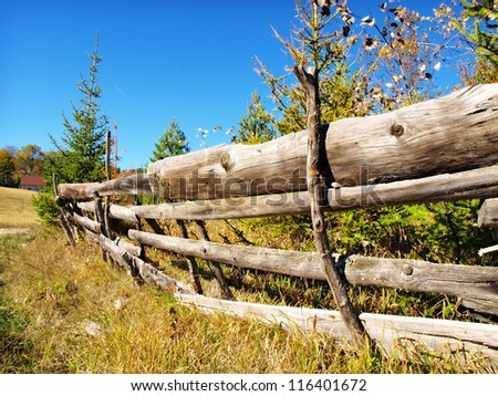 An old wood fence with a green country field behind it - stock photo