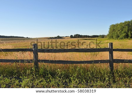 An old wood fence with a green country field behind it. - stock photo