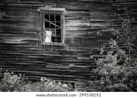 An old wood sided home on the verge of collapse with broken windows - stock photo
