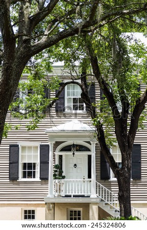 An old wood sided townhouse in Savannah under oak trees - stock photo