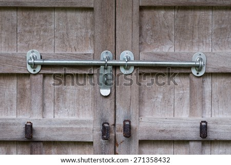 An old wooden door with rusty old locks and newer silver locks - stock photo