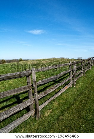 An old wooden fence along a lush, green pasture. - stock photo