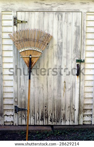 An old wooden rake leans against a dirty work shed. - stock photo