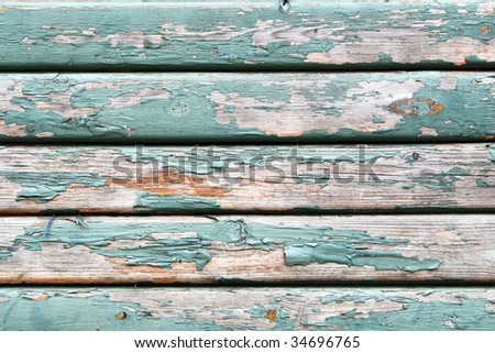 An old wooden wall texture with peeling faded green paint - stock photo