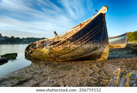 An old wrecked wooden boat on the shore - stock photo