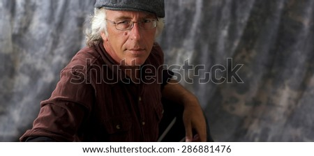An older blue eyed man with glasses and white hair wearing a brown shirt and grey cap against mottled gray background. - stock photo