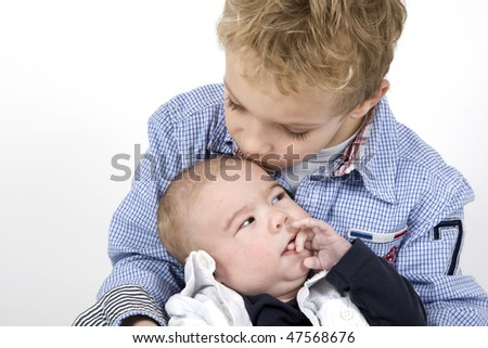 An older brother is kissing his baby brother. - stock photo