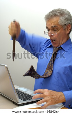An older businessman fed up with his laptop, stabs it with a knife. - stock photo