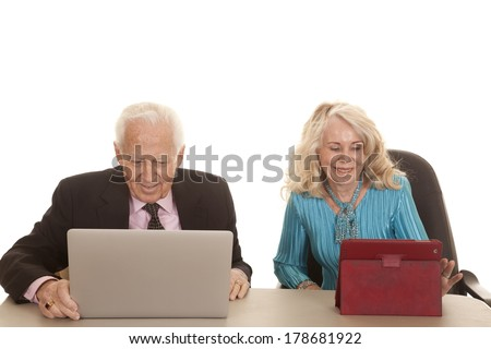 An older couple business people working together on a tablet and computer. - stock photo