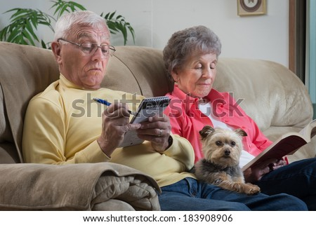 An older couple relaxes together with their lap dog, a cute little Brussels Griffon, keeping them company. - stock photo