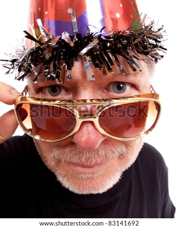 An older goofy guy pulls his sunglasses down and looks at the camera.  He is wearing a birthday party hat. - stock photo