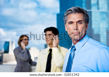 An older grey-haired businessman and his team on mobile phones in a downtown setting.