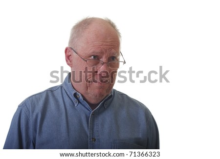 An older man in a blue denim shirt and glasses looking skeptical or confused
