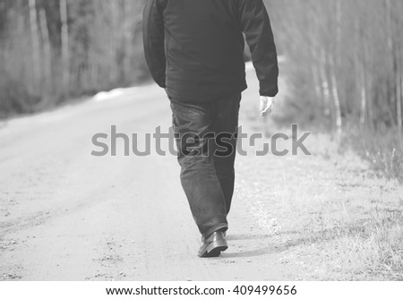 An older man is walking on the road. He is walking away. The man is wearing dark jeans and a black jacket. Image taken during spring time. Image has a vintage effect applied.