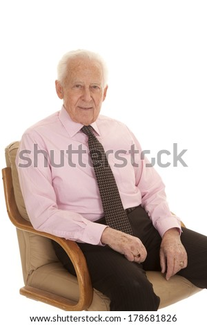 an older man sitting in his chair with a small smile on his lips. - stock photo