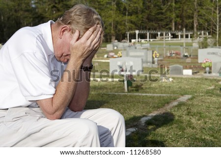 An older man sitting in the cemetery. - stock photo