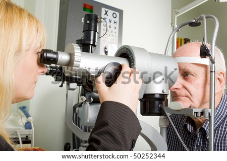 An older man taking an eye test examination at an opticians clinic - stock photo