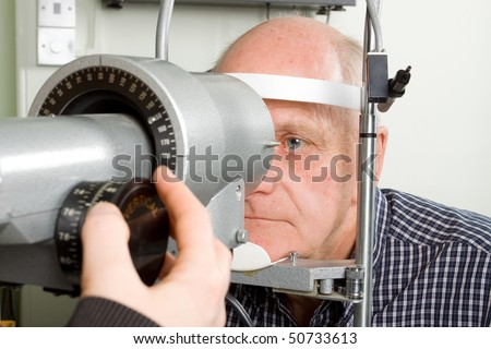 An older man taking an eye test examination at an opticians clinic - stock photo