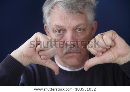 an older man with both thumbs down - stock photo