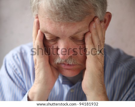 an older man with hands supporting his head, looking down - stock photo