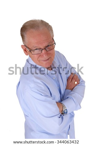 An older man with his arms crossed wearing a blue shirt and looking up